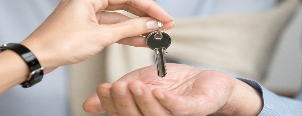 photo of someone giving someone else real estate keys