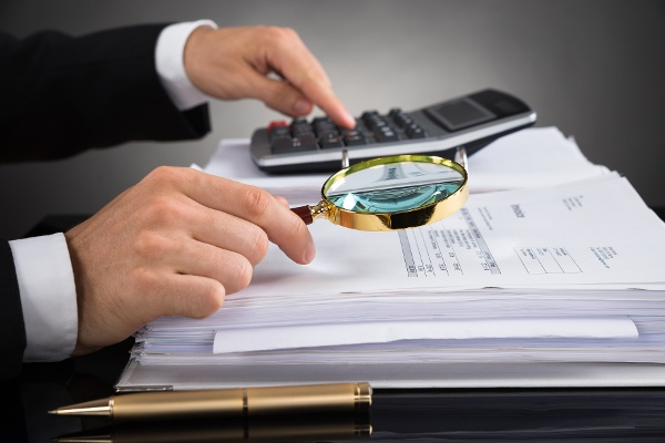 photo of a man looking at someone's finances